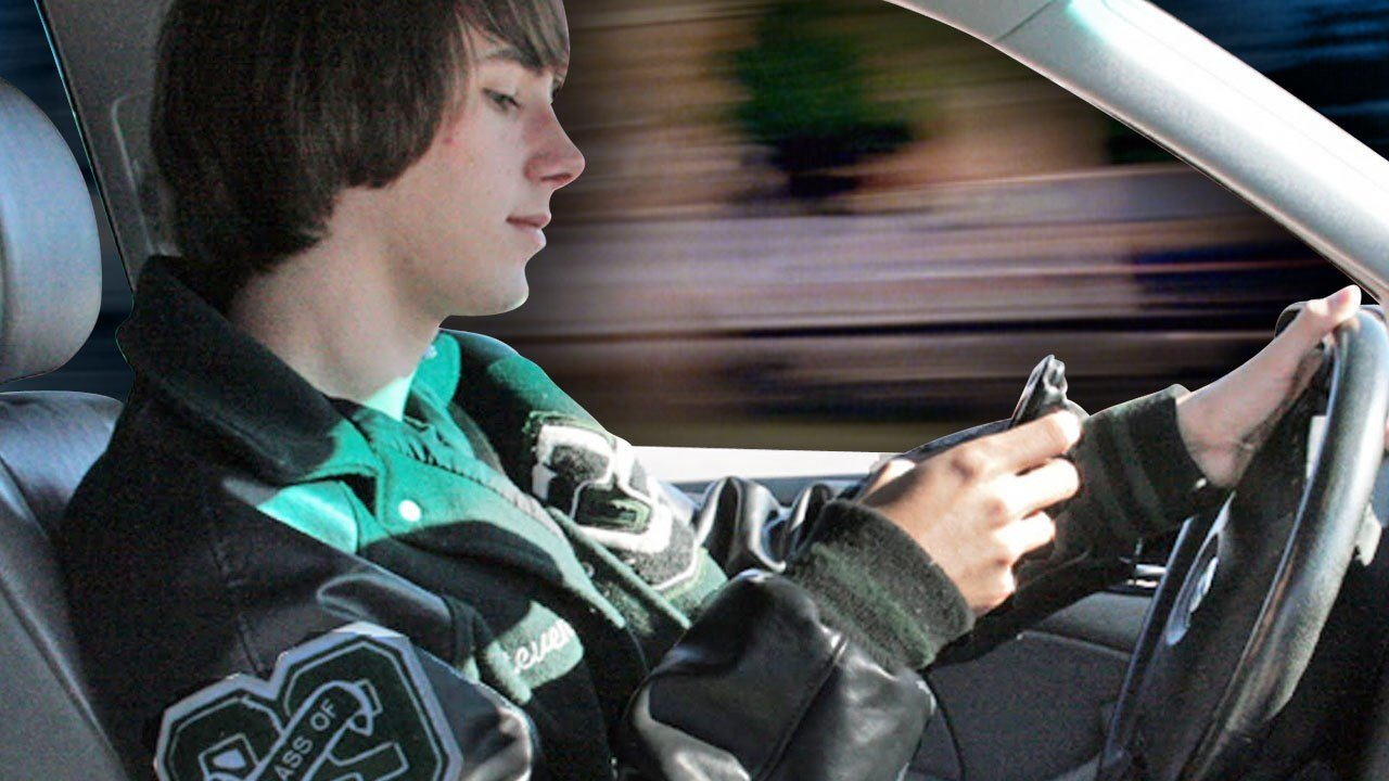 Teenage driver texting behind the wheel with a moving background