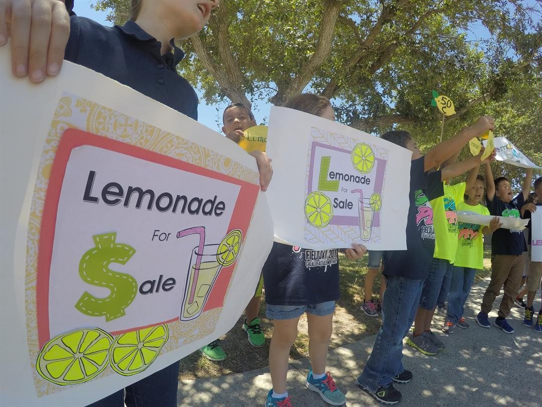 First grade students stood outside on school grounds to advertise their lemonade stand.
