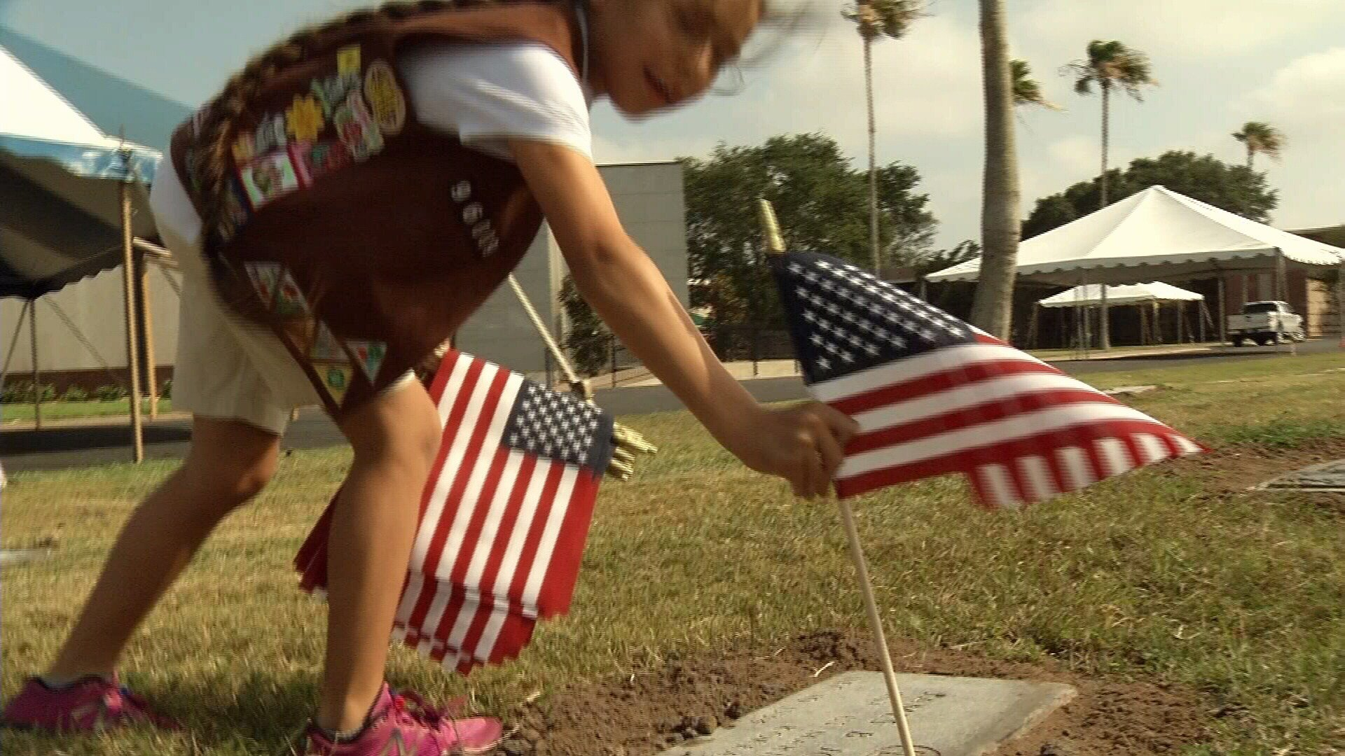 A girl scout places a flag at the headstone of a veteran.