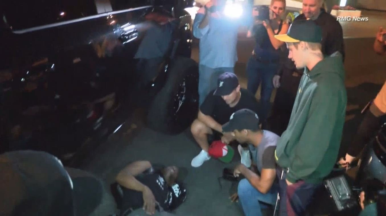 Justin Bieber stands with a photographer after Bieber hit him with his truck.