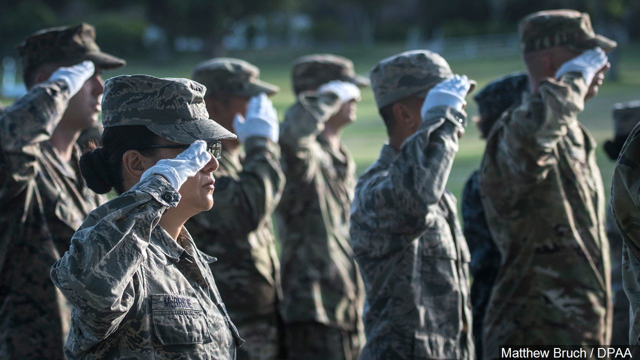PHOTO: Military personnel salute during a ceremony