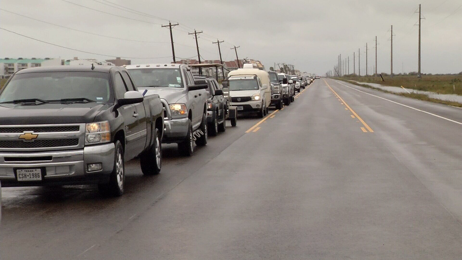 A line of Port Aransas residents waiting in vehicles to cross a checkpoint stretched more than 10 miles down Highway 361.