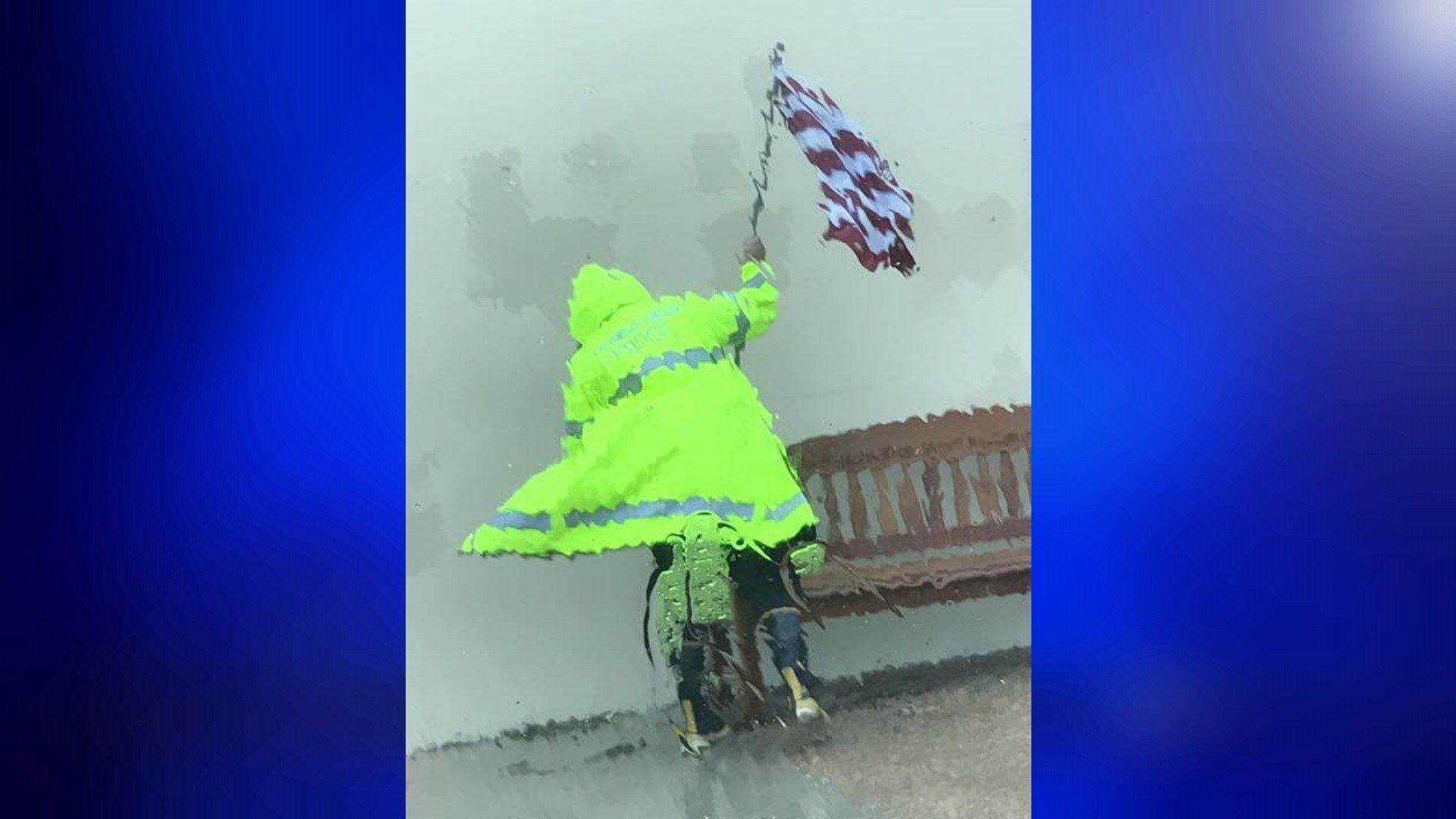 An Aransas Pass police officer holds up an American flag during Hurricane Harvey.