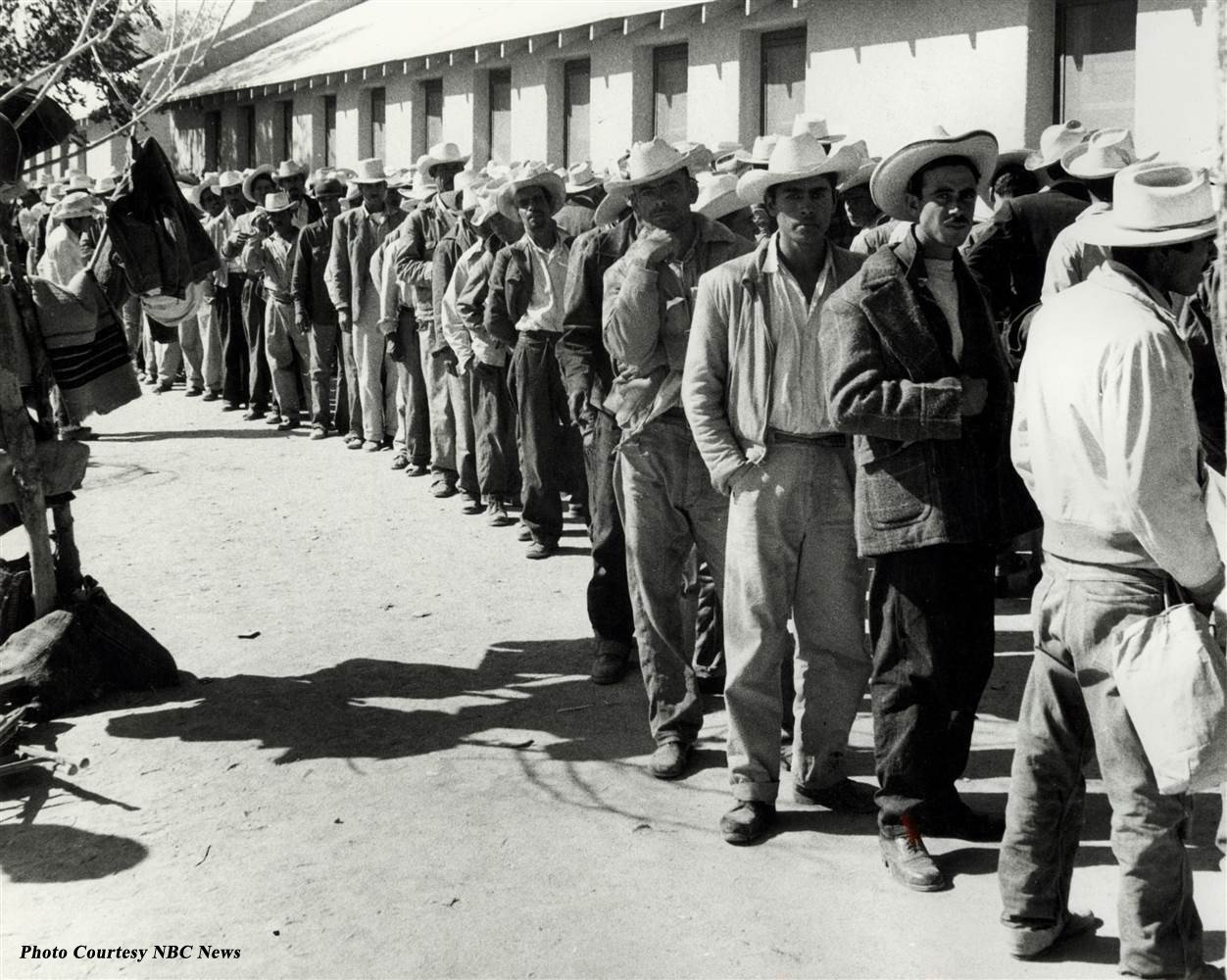 Workers waiting in line to be contracted at a farm reception center.