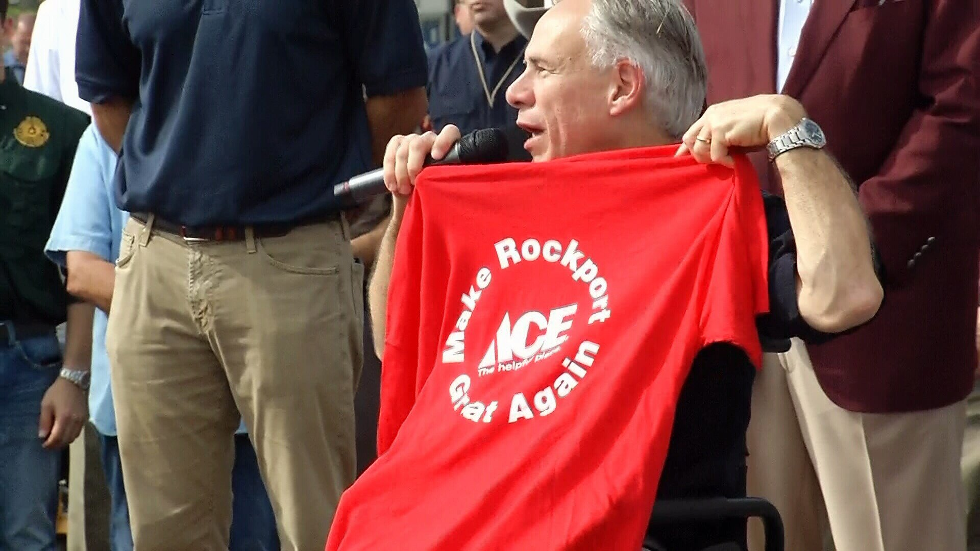 "Governor Greg Abbott displays a ""Make Rockport Great Again"" t-shirt during his joint visit with country music legend George Strait."