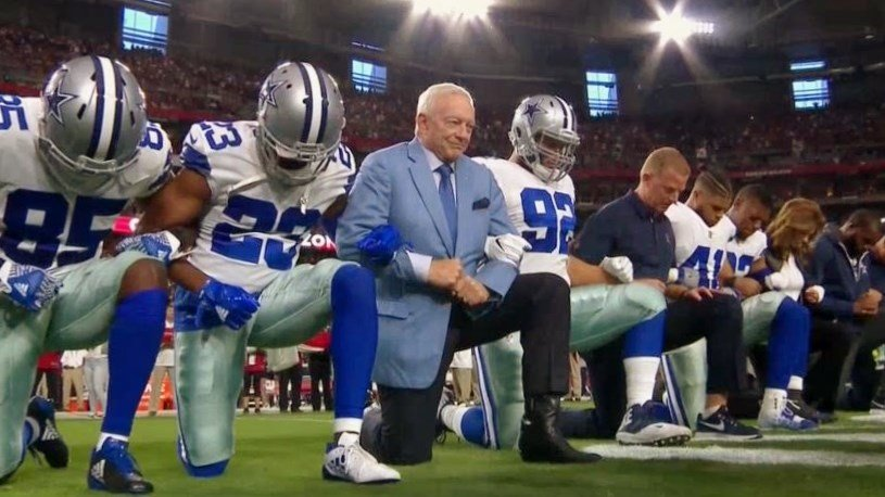 Following a weekend of kneeling and protesting across the NFL, the Cowboys and their owner displayed their own version of unity Monday night, kneeling on the field before rising as a group before the playing of the national anthem. (Courtesy: NBC)
