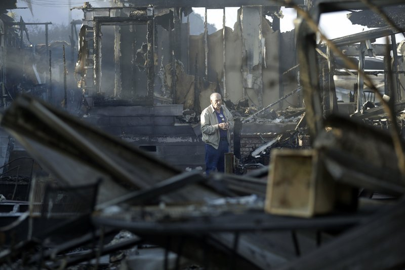 Dick Marsala looks through the debris from his destroyed home after a wildfire roared through his country club neighborhood on Friday, in Bonsall, California. Wind-swept fires have blazed through Southern California, forcing the evacuation of thousands an