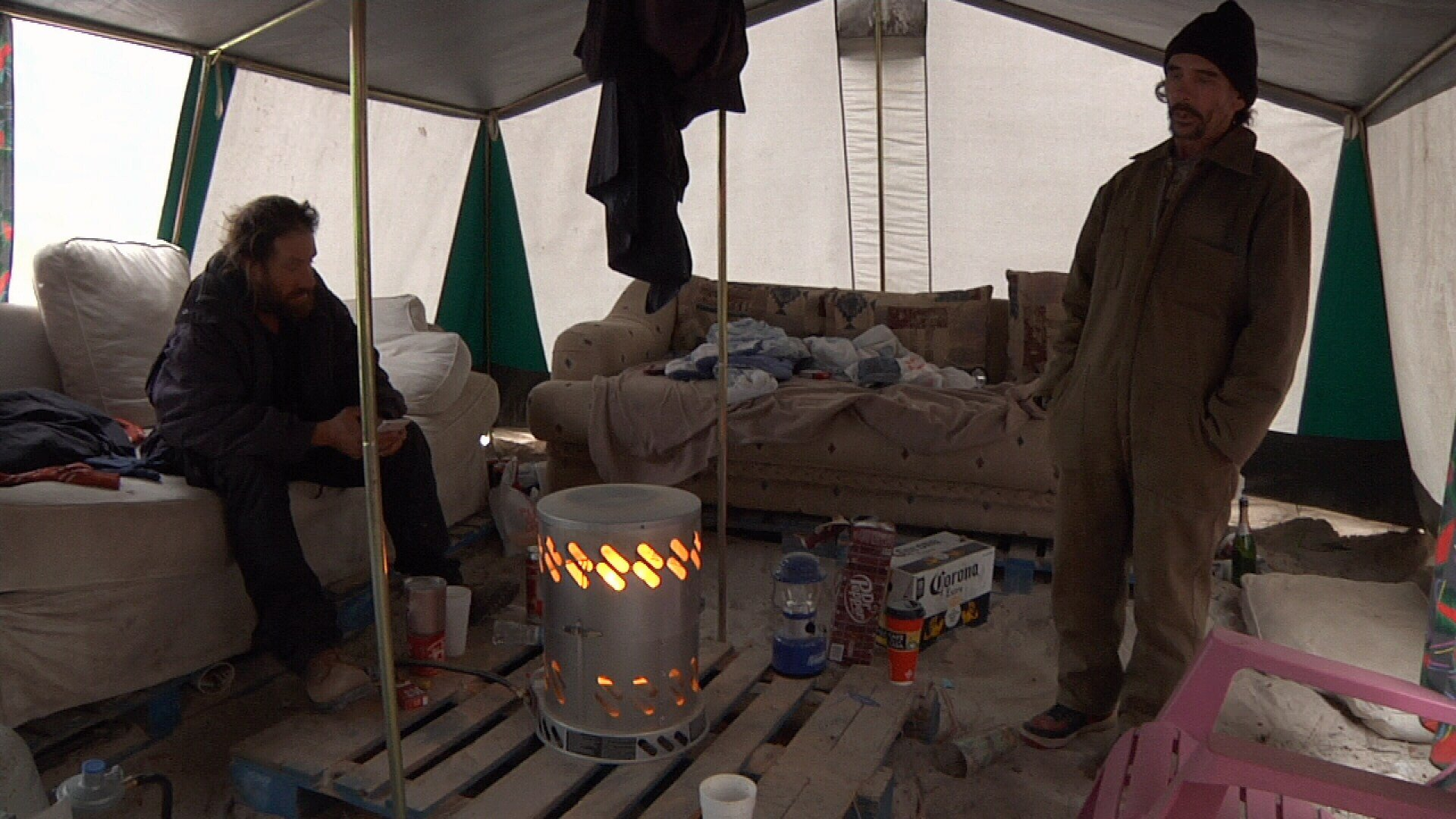 People living in tents use heaters and many blankets to stay warm.