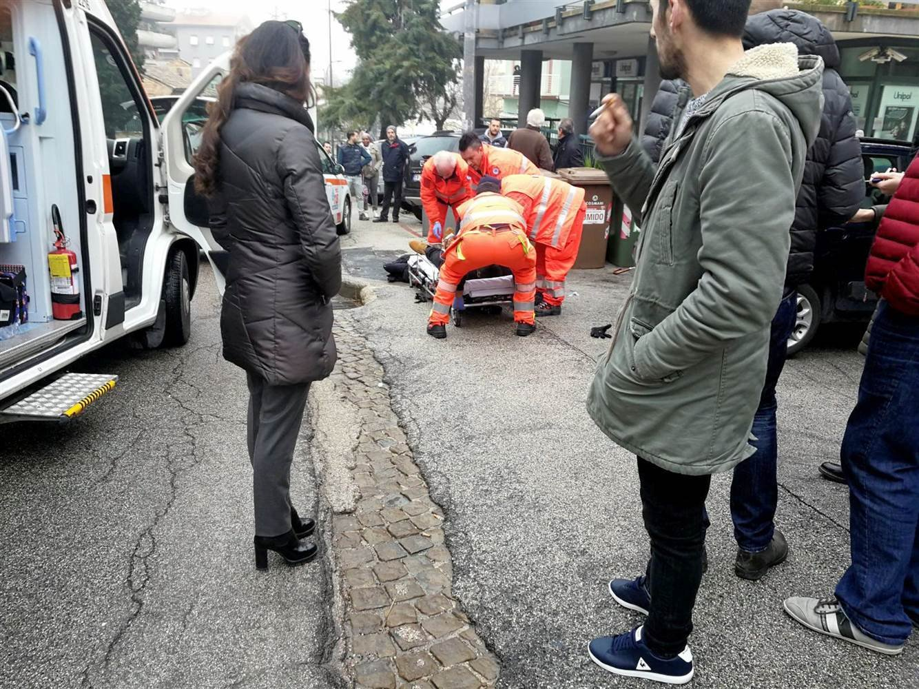 Healthcare personnel take care of an injured person after being shot by gun fire from a vehicle, in Macerata, Italy, on Feb. 3, 2018. photo NBC News.