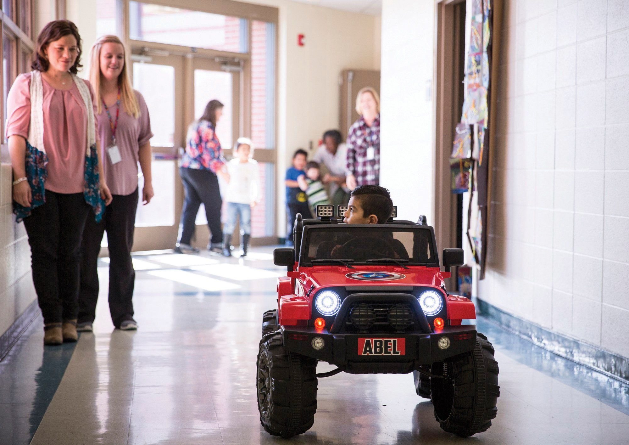 Abel Salazar, 4, drives a battery-operated Jeep in the halls of Dudley Elementary School, while his therapists and classmates watch. Photo: Angela Piazza, Victoria Advocate