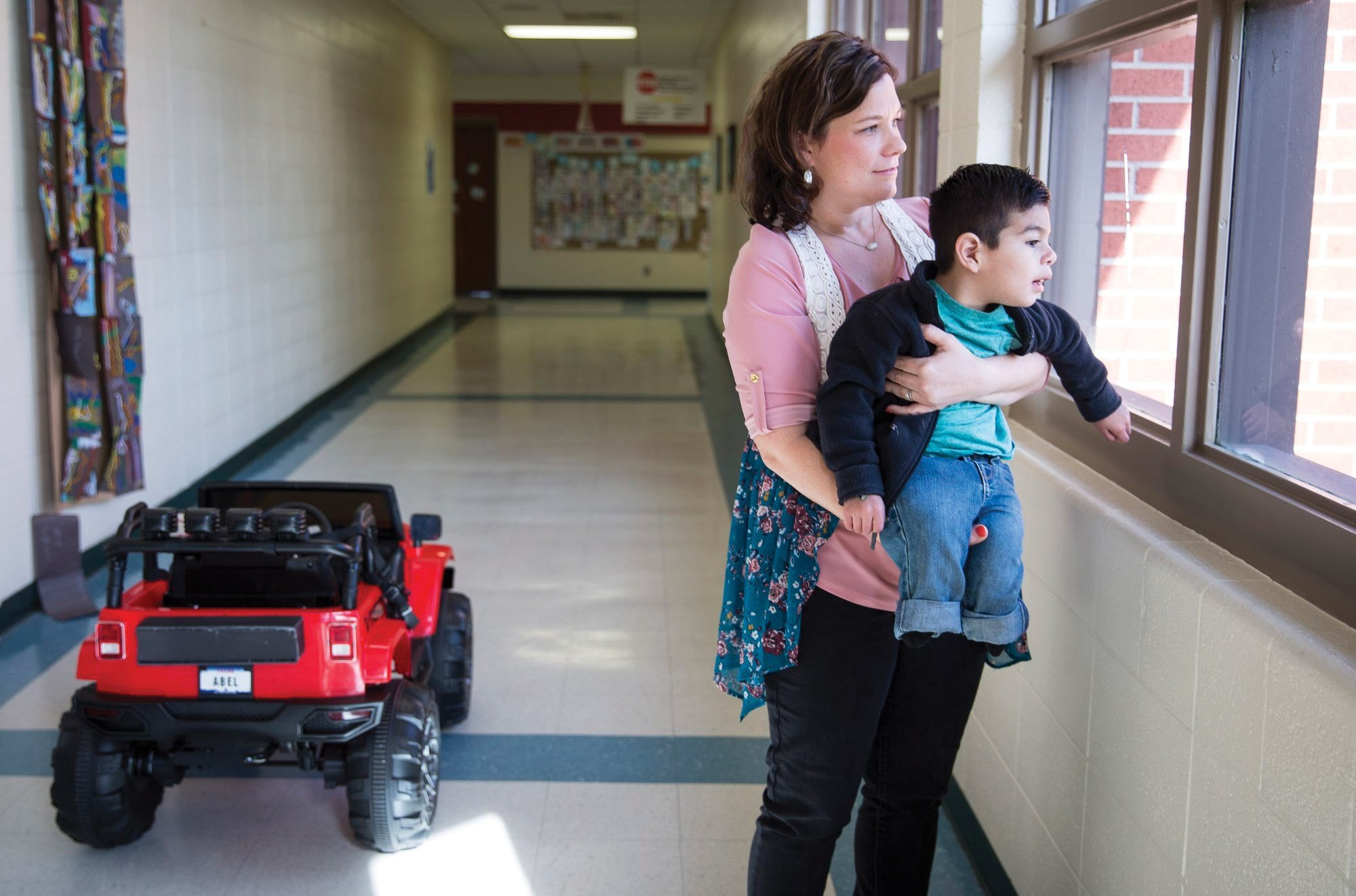 Occupational therapist Amanda Kern holds up Abel Salazar, 4, so he can look out the window at Dudley Elementary School. photo  Angela Piazza, Victoria Advocate