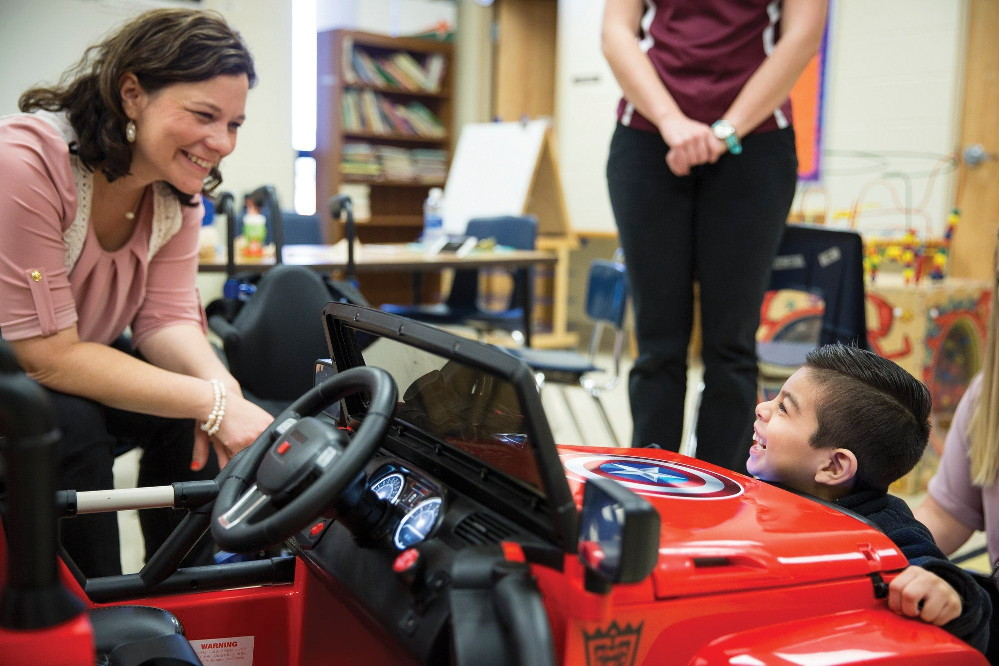 Abel Salazar, 4, laughs with occupational therapist Amanda Kern after unlatching the hood of his battery-operated Jeep at Dudley Elementary School. photo Angela Piazza, Victoria Advocate