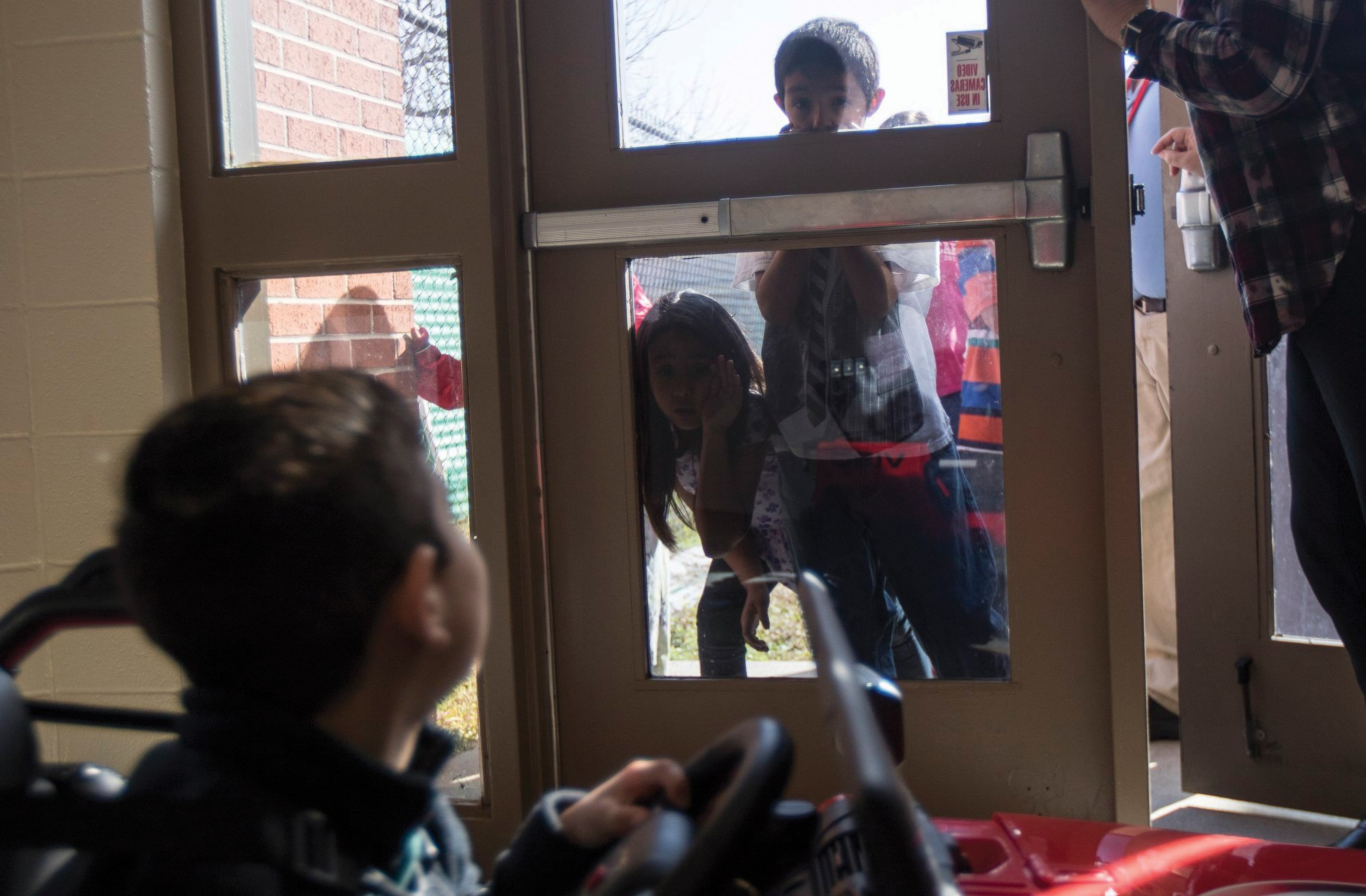 Abel Salazar, 4, drives a battery-operated Jeep in the halls of Dudley Elementary School. Third-grade students press their faces against a glass door to watch the Go Baby Go Jeep drive past. photo Angela Piazza, Victoria Advocate