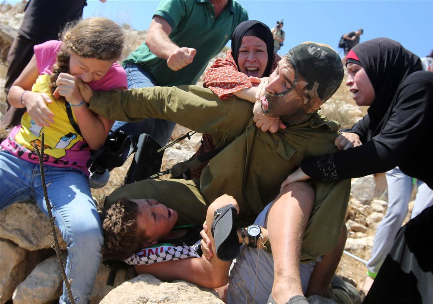 Tamimi, far left, is seen biting an Israeli soldier. Photo courtesy of NBC.