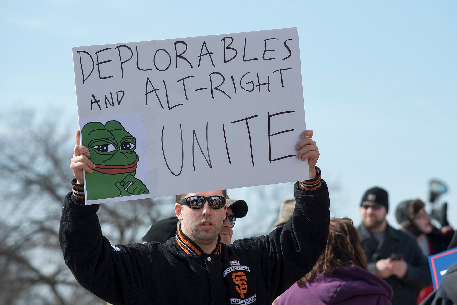 wikipedia: Pepe the frog/  An alt-right activist holds up a sign featuring Pepe at the March 4 Trump in Saint Paul, Minnesota.