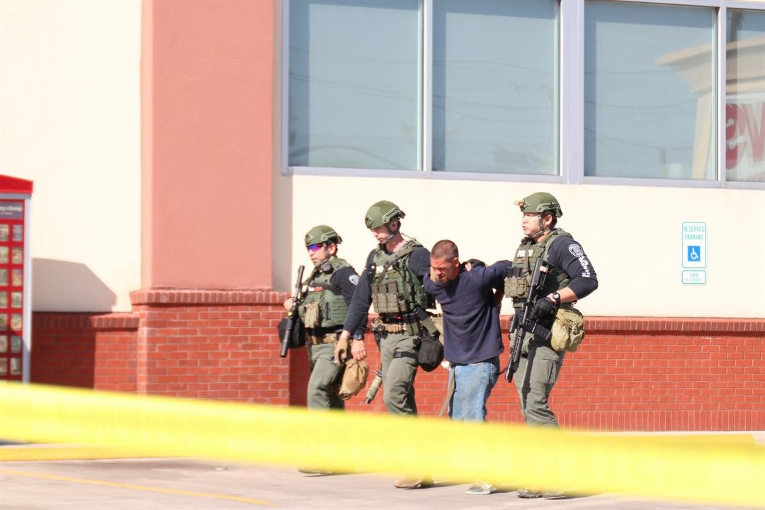 Officers with the SWAT team take the suspect into custody.