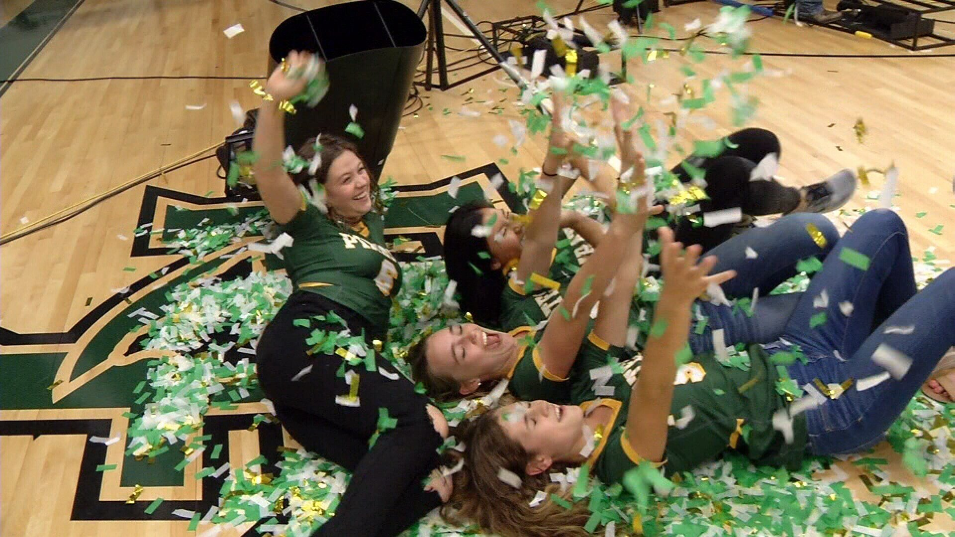 Volleyball players role in confetti after Ellen tells them they will have a new gym thanks to a $1 million donation from Lowes.