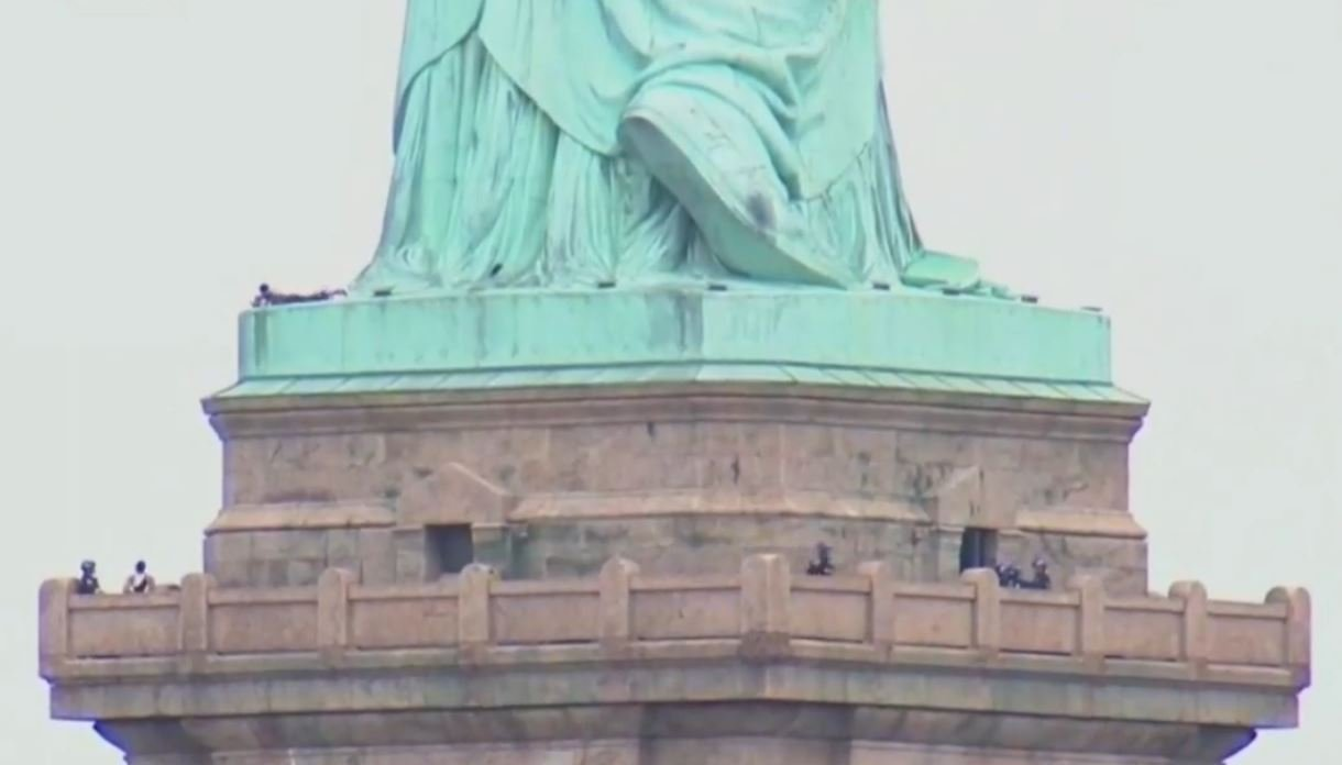 Protester Climbs On Statue Of Liberty