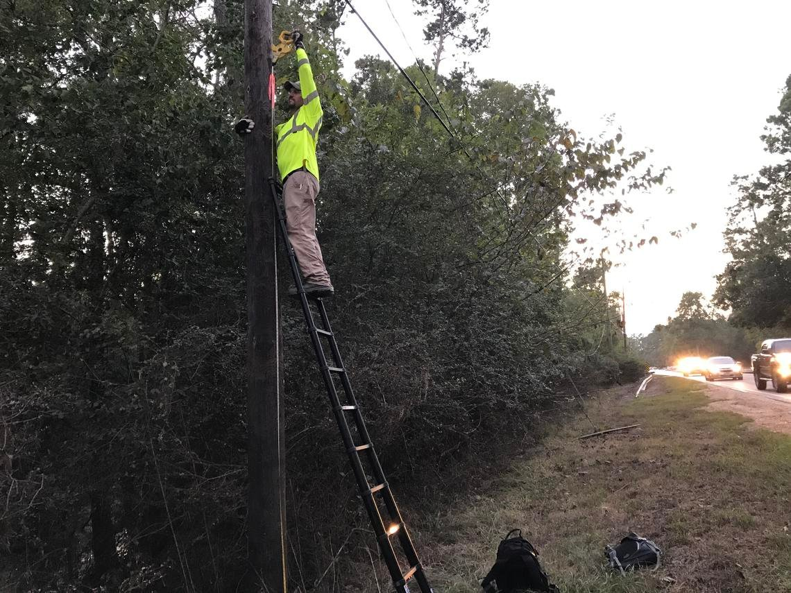 USGS hydrologic technician Brandon Cooper flags a debris line on a telephone pole approximately 14.3 feet above the ground and located about 245 feet east of the bridge on Keith Road over Boggy Creek on September 15, 2017.  Credit: Melissa Null, USGS.