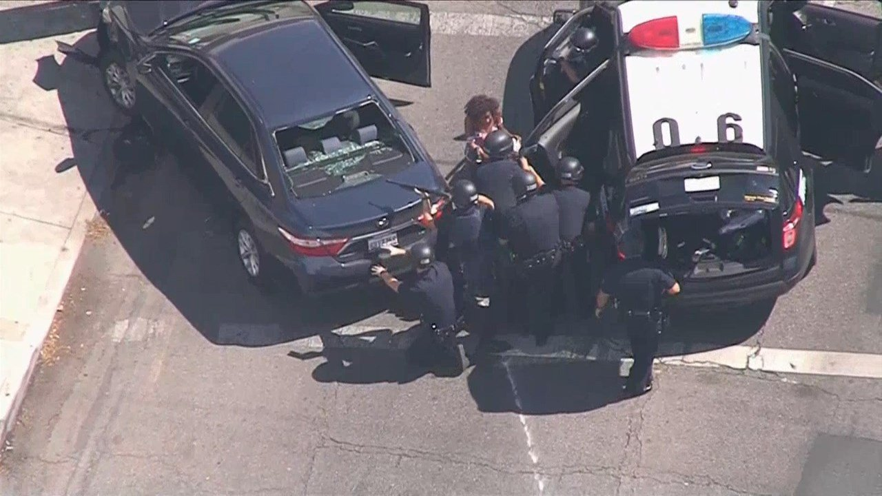 Authorities in Los Angeles say a woman was killed after a gunman being chased by police fled into a supermarket and took hostages. (NBC)