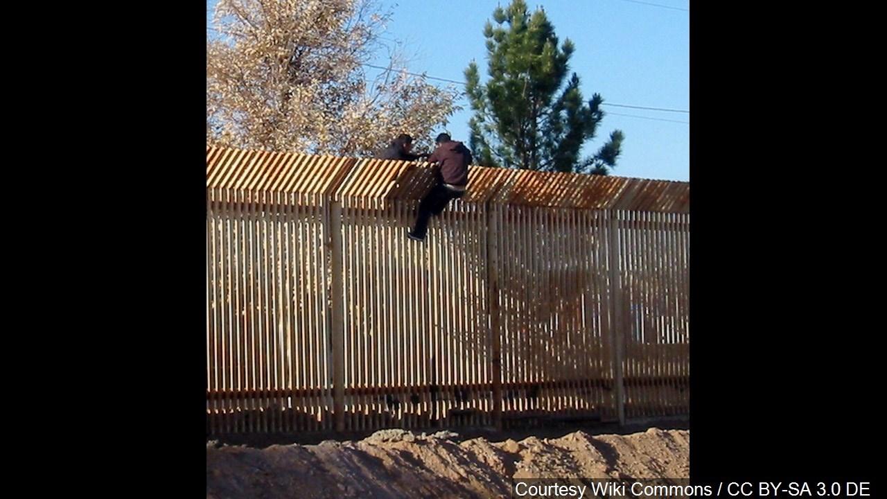 two men scale the border fence into mexico 1 500 footlong concrete