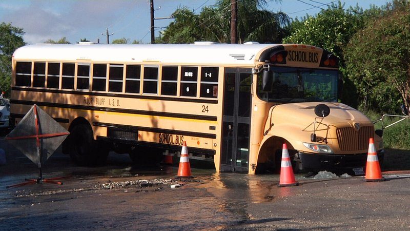 A bus got stuck in a sinkhole after the driver tried to get through a  flooded